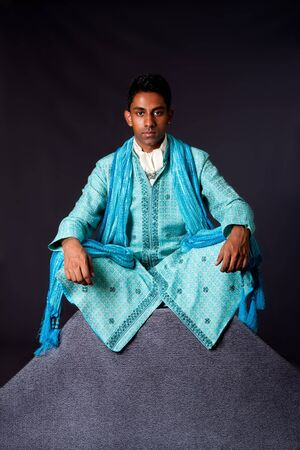 dhoti: Beautiful authentic Indian hindu man in typical ethnic groom attire sitting in lotus position with legs crossed on top of rock. Bangali male wearing a light blue agua decorated Dhoti with shawl.