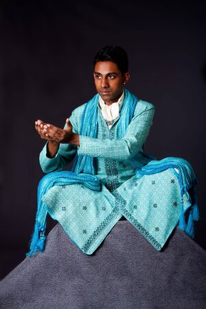 dhoti: Beautiful authentic Indian hindu man in typical ethnic groom attire sitting in lotus position with legs crossed on top of rock and sticking hands out to receive a gift. Bangali male wearing a light blue agua decorated Dhoti with shawl.