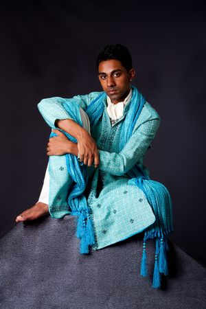 dhoti: Beautiful authentic Indian hindu man in typical ethnic groom attire sitting relaxed on top of rock leaning on knee. Bangali male wearing a light blue agua decorated Dhoti with shawl.