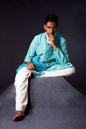 dhoti: Beautiful authentic Indian hindu man in typical ethnic groom attire sitting and thinking on top of pyramid rock. Bangali male wearing a light blue agua decorated Dhoti with shawl.