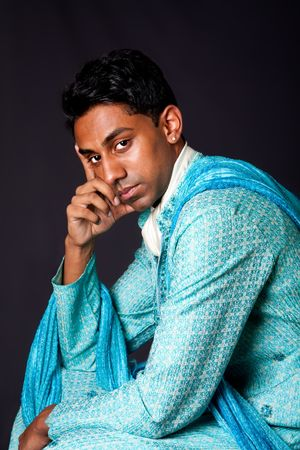 dhoti: Beautiful face of an Indian Hindu young man with earring wearing blue Dhoti. Portrait of handsome Desi male sitting and thinking, isolated.