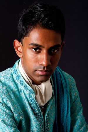 dhoti: Beautiful face of an Indian Hindu young man with earring wearing blue Dhoti. Portrait of handsome Desi male, isolated.