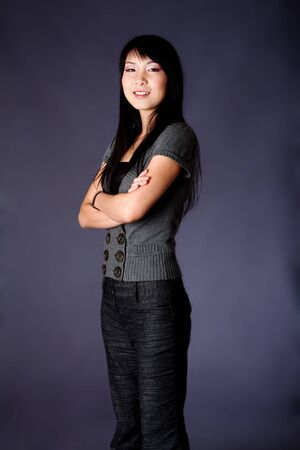 Beautiful Asian American business career woman standing in grey casual clothes with arms crossed, isolated.