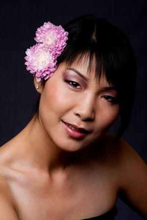 Beautiful shaded face of an Asian-American woman with purple pink white flowers in her hair.