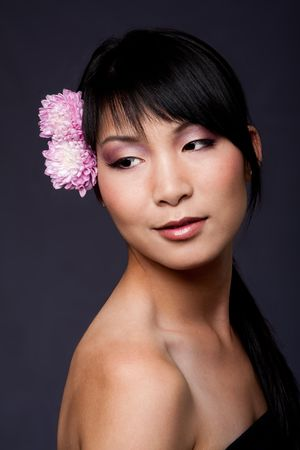 Beautiful face of an Asian-American woman with purple pink white flowers in her hair, looking to her side, isolated.