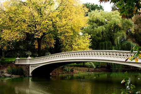 Beautiful fall autumn scenery landscape of a white bridge over a peaceful body of water lake river.