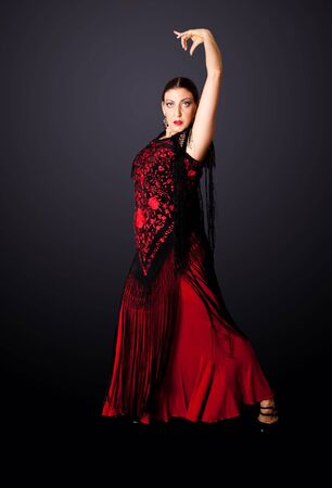 Beautiful female Spanish Flamenco dancer doing a typical line pose, wearing modern attire. Spanish woman dancing Paso Doble in red and black dress clothes, isolated.