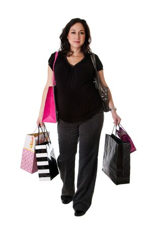 Beautiful happy Caucasian pregnant brunette woman holding shopping bags while walking, isolated Stock Photo - 5837309