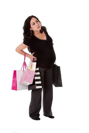 back ache: Beautiful Caucasian pregnant brunette woman holding shopping bags while standing and having back pain, isolated