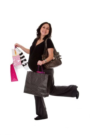 Beautiful happy exciting smiling Caucasian pregnant brunette woman holding shopping bags while walking and having her leg up, isolated