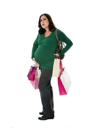 tired: Beautiful Caucasian pregnant brunette woman holding shopping bags while standing expressing pain and holding belly as if her water broke, isolated