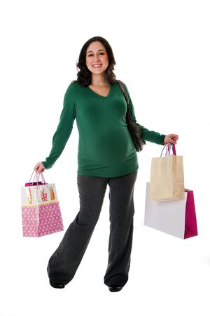 Beautiful happy exciting smiling Caucasian pregnant brunette woman holding shopping bags while standing, isolated