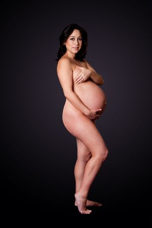 Beautiful naked pregnant Caucasian brunette woman, isolated. Hispanic Latina girl in bare skin showing belly while covering her breasts. Stock Photo - 5946577
