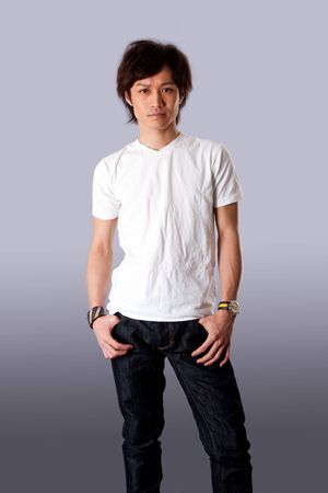Casual Asian man wearing white shirt and jeans standing with thumbs in pockets, isolated.