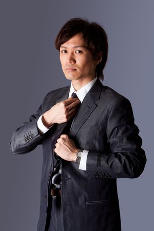 Successful Asian business man standing with confidence and fixing his necktie, isolated.