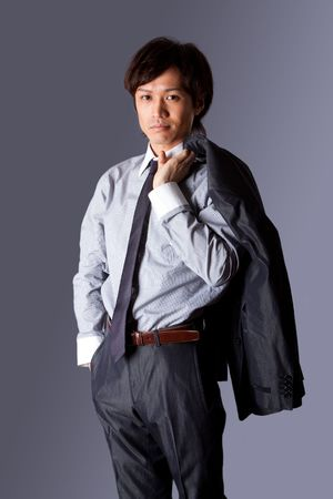 Successful Asian business man standing with confidence and jacket over his shoulder and hand in pocket, isolated. photo