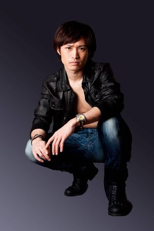 Handsome Asian male wearing leather jacket over a bare chest and jeans with macho attitude while crouching, isolated.