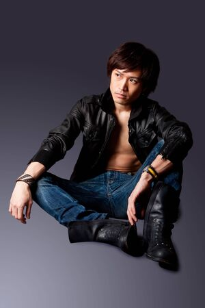 Handsome Asian male wearing leather jacket over a bare chest and jeans with macho attitude while sitting on floor expressing thought, isolated. photo