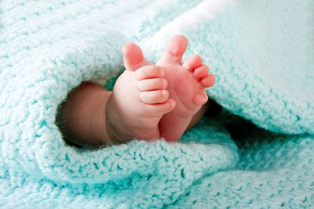 Two cute tiny baby feet wrapped in a blue-green aqua knitted blanket.