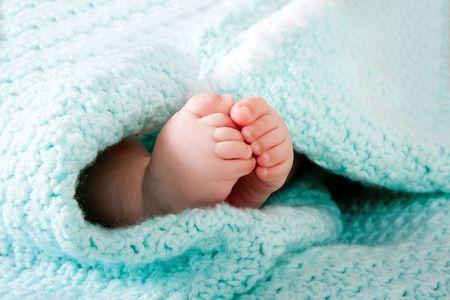 pie bebe: Dos pies de lindo beb� peque�o envuelven en una manta tejida de aqua azul verdoso.