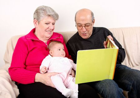 Happy fun Caucasian Hispanic Middle Eastern family sitting together on couch reading book to baby. Grandfather and Grandmother reading green book to infant granddaughter.