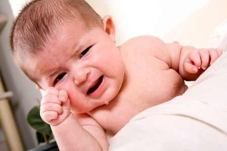 Face of an unhappy unisex Caucasian Hispanic baby crying with tears while rubbing eye. photo