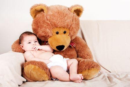 teddy bear: Cute Caucasian Hispanic unisex baby in arms of a big brown stuffed teddy bear sitting on couch.