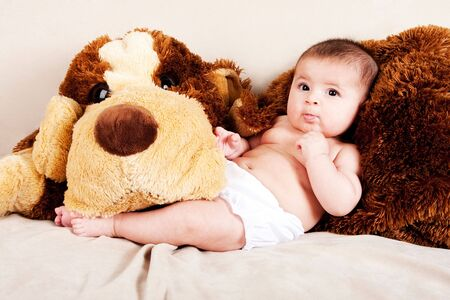Cute Caucasian Hispanic unisex baby in arms of a big brown stuffed dog laying on couch. photo