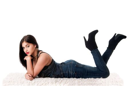 denim jeans: Beautiful sexy fashion girl with red lips laying playful on fluffy cotton with legs in the air, isolated.