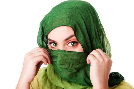 penetrating: Portrait of mysterious beautiful Caucasian Hispanic Latina woman face with green penetrating eyes and holding green fashion scarf with hands in front of mouth and wrapped around head, isolated. Stock Photo