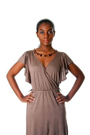 assertive: Beatiful African American business woman standing with hands on hips wearing a gray fashion dress and amber necklace, isolated.