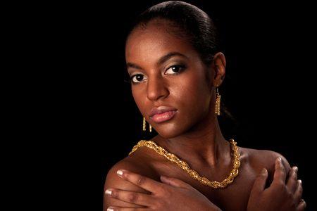 rijke vrouw: Gezicht van de prachtige Afrikaanse Amerikaanse vrouw met gouden oor ringen en ketting, geïsoleerd.