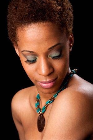 parpados: Hermosa cara de un modelo de moda femenina estadounidense mirando hacia abajo mostrando sus p�rpados con sombras de verde y largas pesta�as, al descubierto los hombros y llevando un verde con collar marr�n, aislados.