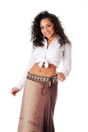 Happy smiling beautiful Caucasian Hispanic Latina young woman with brown curley hair. Cute tanned brunette, ethnic girl in white knotted shirt and brown skirt dancing showing belly button, isolated. photo