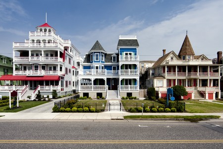 Colorful Victorian style houses alongside a road. Beautiful wooden homes with balconies and porches, painted red, blue, white and orange, under a blue summer spring sky, in Cape May, NJ.