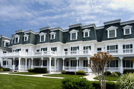 row houses: Verde con le case di riga bianca in legno stile vittoriano con erba di fronte sotto un cielo blu.