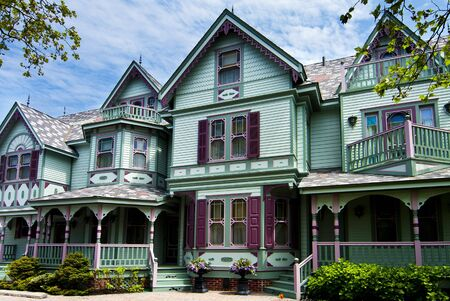 Beautiful big old nostalgic historic wooden green with purple Victorian house building with porch.