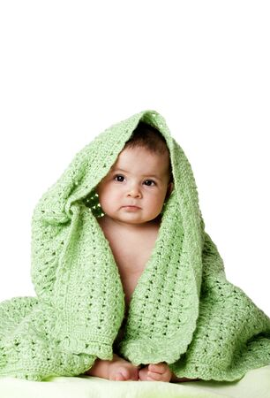 Beautiful cute innocent Caucasian Hispanic baby face while sitting and covered between green knitted blankets, isolated. Archivio Fotografico
