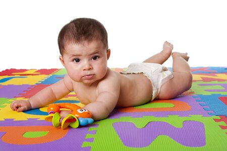 Beautiful cute happy Caucasian Hispanic baby laying on belly on a colorful padded floor tiles with alphabet letters and a toy, isolated. Imagens