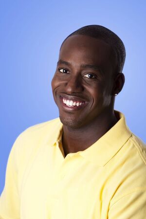 Face of handsome happy African American corporate business man smiling, wearing yellow polo shirt on a blue sky-like background.