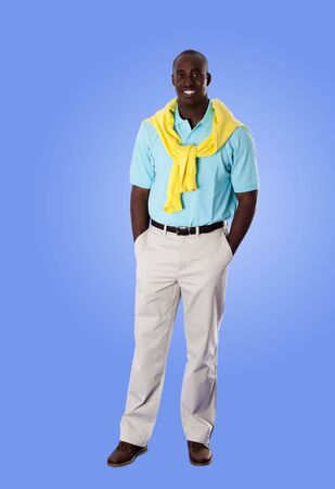 khakis: Handsome happy African American corporate business man smiling, standing with hands in pocket, wearing blue shirt and yellow sweater around his neck and khakis, isolated.