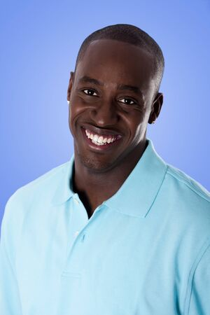 Face of handsome happy African American corporate business man smiling, wearing blue polo shirt, isolated.