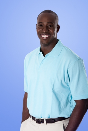 Handsome happy African American corporate business man smiling, wearing blue polo shirt, hands in pocket, standing, isolated.