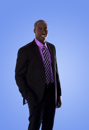 Handsome happy African American corporate business man smiling, wearing black suit with purple shirt, standing with hand in pocket,  isolated. Stock Photo