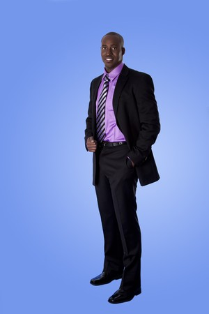 authoritative: Handsome happy African American corporate business man smiling, wearing black suit with purple shirt, standing with authority with hand in pocket,  isolated.