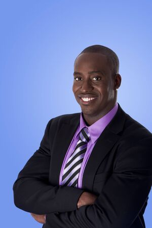 sincere: Handsome happy African American corporate business man smiling, wearing black suit with purple shirt, arms crossed,  isolated.