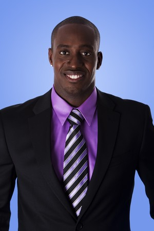 Handsome happy African American corporate business man smiling, wearing black suit with purple shirt and striped necktie,  isolated.