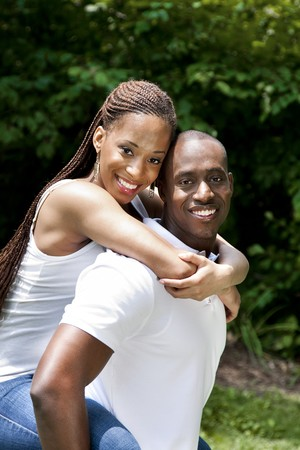Beautiful happy smiling laughing young African American couple piggyback playing in the park, woman hugging man, wearing white shirts and blue jeans. photo