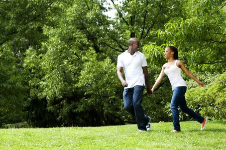 Beautiful fun happy smiling African American young couple running playing in park, wearing white shirts and blue jeans.