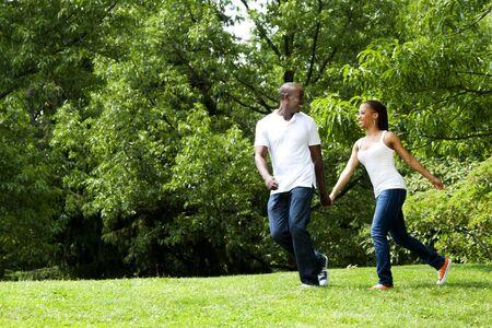 garcon africain: Happy souriant running afro-am�ricaine jeune couple jouant dans le parc, porter des chemises blanches et blue jeans magnifique fun.